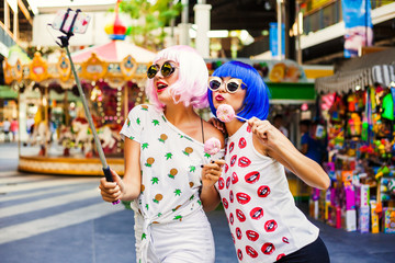 Two bright funny cool fashionable girl in blue and pink wigs, make selfie on background carousel at an amusement park. In the hands holding the sweet donuts.