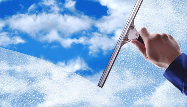Employee cleaning a glass with rain drops and blue sky