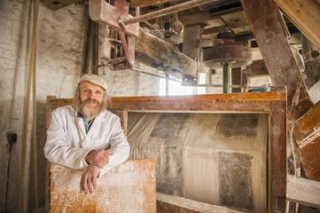 Caucasian artisan smiling in flour mill