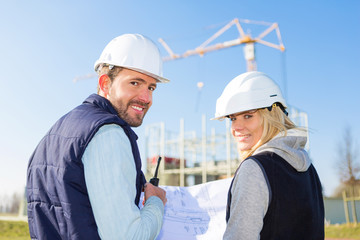 Two workers working outside on a construction site