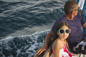 Father and daughter sitting on boat