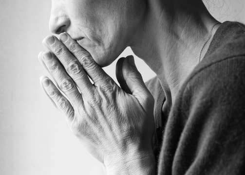 Mature woman in profile with hands clasped in prayer (cropped and black and white)
