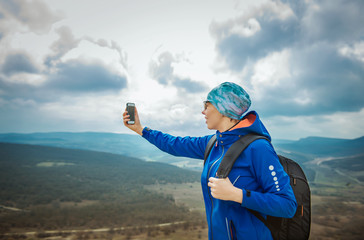 girl tourist on background of the mountains with a mobile phone