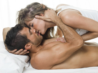 attractive couple in love under white bed sheets