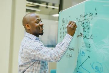 Black businessman writing on whiteboard