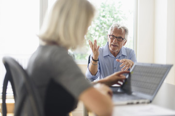 Older Caucasian business people arguing in office meeting