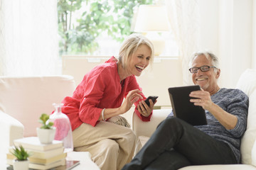 Older Caucasian couple using technology in living room