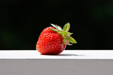 One juicy strawberry on wood railing, bright summer day outdoors with black background..