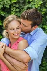 Romantic man kissing woman at front yard