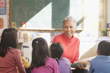 Mixed race teacher reading to students in classroom
