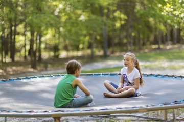 Caucasian children sitting on trampoline