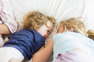 Caucasian brother and sister playing on bed