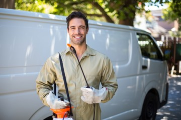 Smiling worker with pesticide sprayer