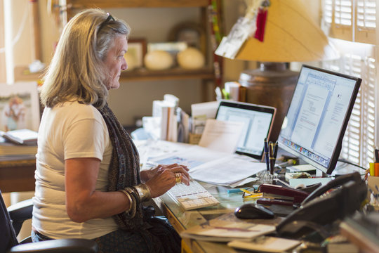 Older Caucasian woman working on computer at desk