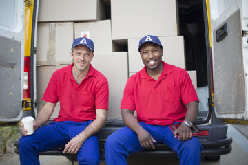 Delivery men sitting with packages in van