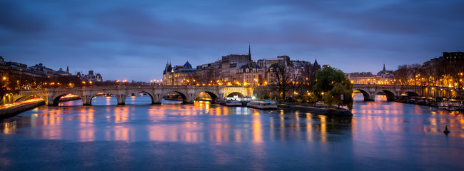 Dawn on a cloudy morning in Paris, with Ile de la Cite, Pont Neuf and the Seine River reflecting city lights. France