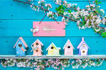 Welcome sign hanging over row of colorful birdhouses and spring blossoms