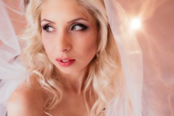Beautiful emotional blonde bride posing under veil, face closeup