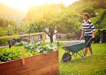 Frau arbeitet im Garten am Hochbeet-gardening 15