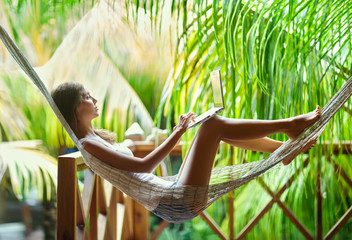 Young woman lying in a hammock with laptop