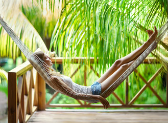 Young woman relaxing in hammock in a tropical resort