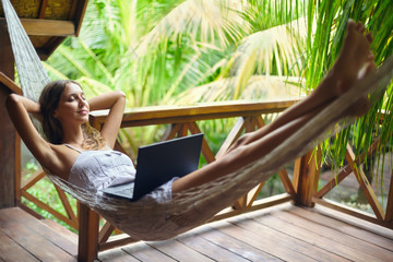 Young woman relaxing in a hammock with laptop in a tropical reso