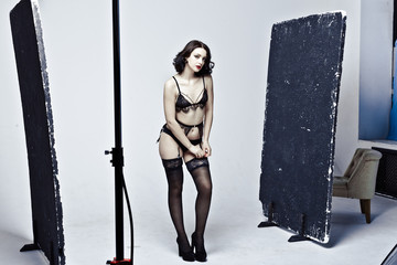 Beautiful lingerie model posing in studio photography. Backstage