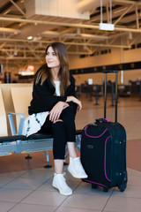 Air travel concept with young casual woman sitting with hand luggage suitcase in terminal while waiting for her flight.