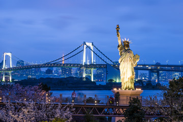 Statue of Liberty and Rainbow bridge, located at Odaiba Tokyo, with Tokyo skyline in background at twilight