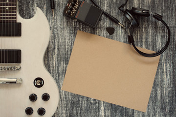 electric guitar on wooden background, sheet of paper, earphone, Overdrive Effects Pedals