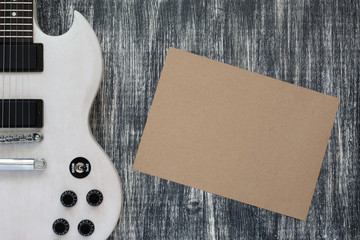 electric guitar on wooden grey background, sheet of paper
