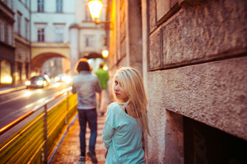 Romantic young couple walking & holding hands in Prague street