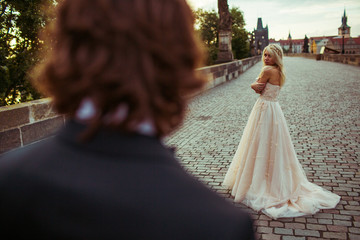 Handsome romantic groom looking at beautiful blonde bride outdoo