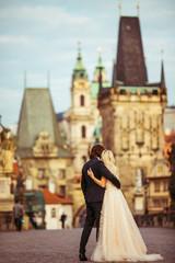 Romantic newlywed couple on honeymoon, hugging on bridge in Prag
