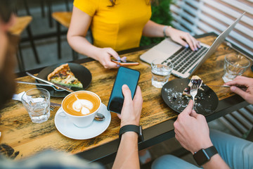 Smartphones in  hands over the table with coffee and laptop