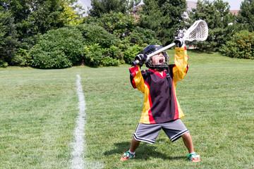 Child playing lacrosse screams in celebration joy while holding