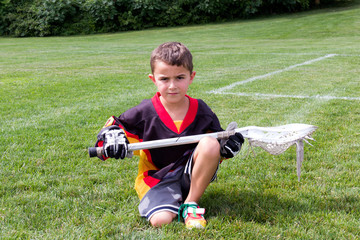 Little boy lacrosse player in the park kneeling down and posing