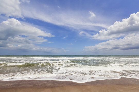 Gentle waves on a sandy beach are captured under a cloudy blue sky at Cocoa Beach, Florida.