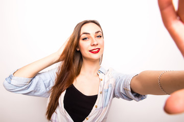 Young beautiful girl taking Selfie picture from hands  over white