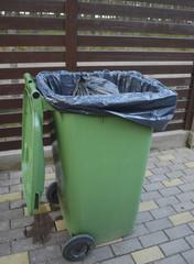 Opened green dumpster on brown wooden fence background. Black bag of trash with strings is inside dumpster.
