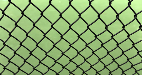 Blash mesh fence over green background. Angled