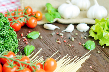 Tomatoes, spaghetti, parsley and garlic on wooden table
