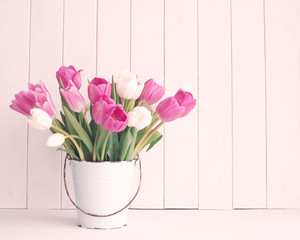 Pink and white tulips in a vintage white tin bucket