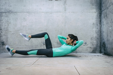 Young woman performing core crunch exercise