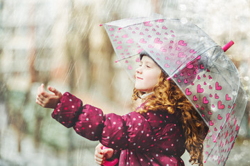 Little girl stretches her hand to catch falling raindrop.