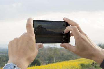 Hands of man, making photo of summer landscape by his smart phone