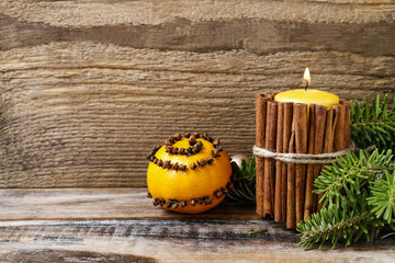Candle decorated with cinnamon sticks and orange pomander ball