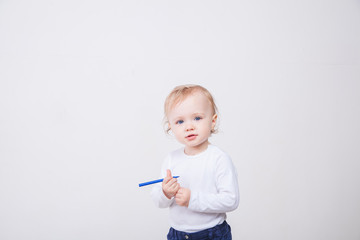 Baby girl drawing with colorful felt-tip pens on white background