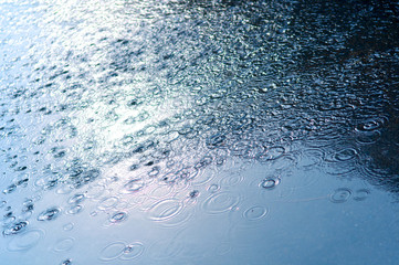 Rain drops background with blue sky reflection and water circles on dark asphalt, on the road