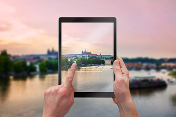 Photographing city landscape with tablet. Tourists holding a black tablet.
